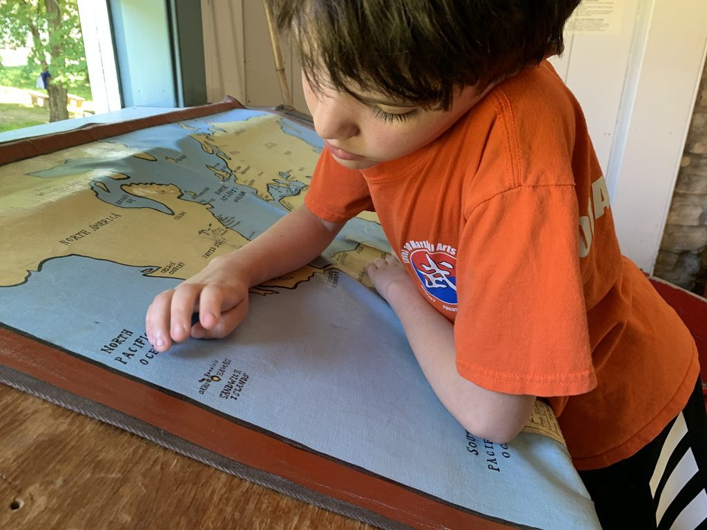 A boy looks at a map of the world and dreams of what he will be when he grows up